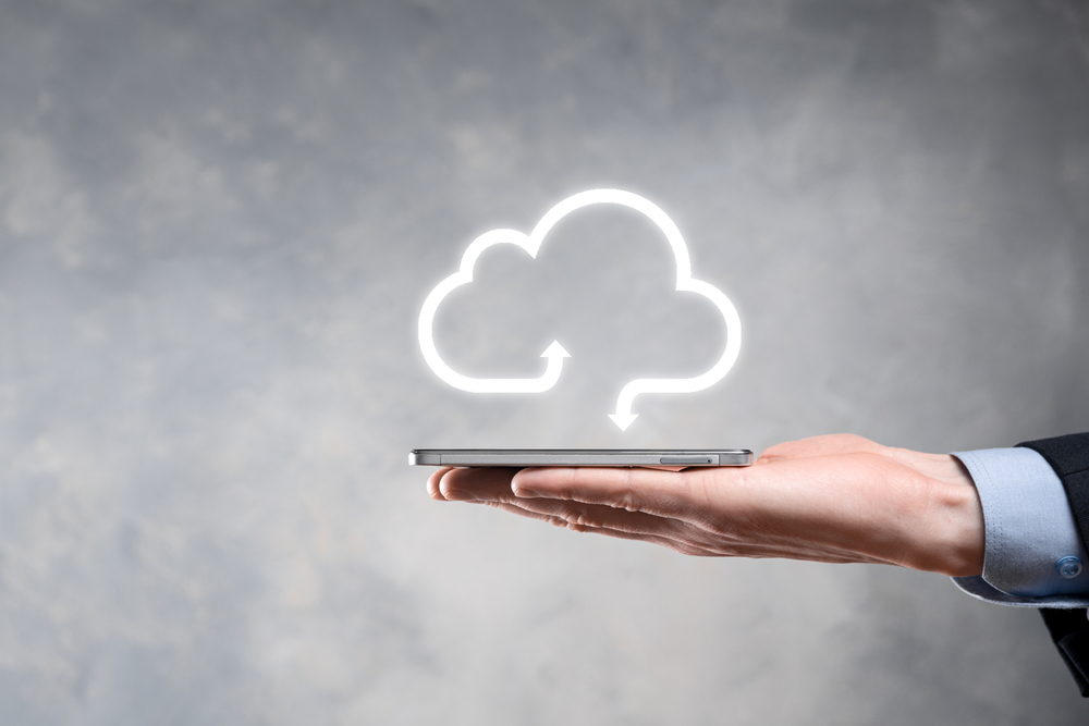 Man Holding Smartphone in Hand With Cloud Computing Logo Over It